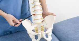 Doctor pointing to a spot where a common spinal injury occurs
