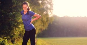 woman squeezing her back in pain from exercise