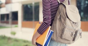 Student wearing a backpack and carrying books to school