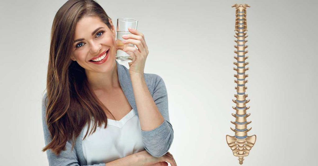 woman with glass of water next to a spine